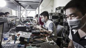 Tehnicienii fac reparații la mașinile de extragere a bitcoinului la o instalație minieră operată de Bitmain în Ordos, Mongolia Interioară,